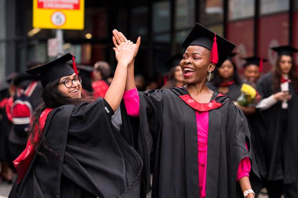 Smiling graduates giving a high-five