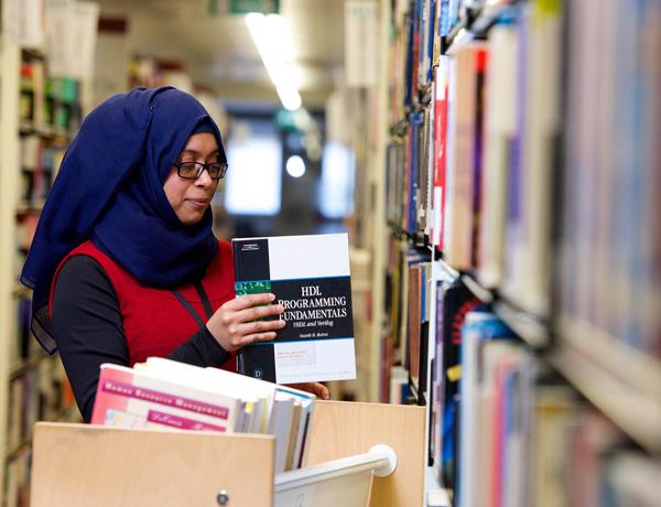 Library staff member arranging books