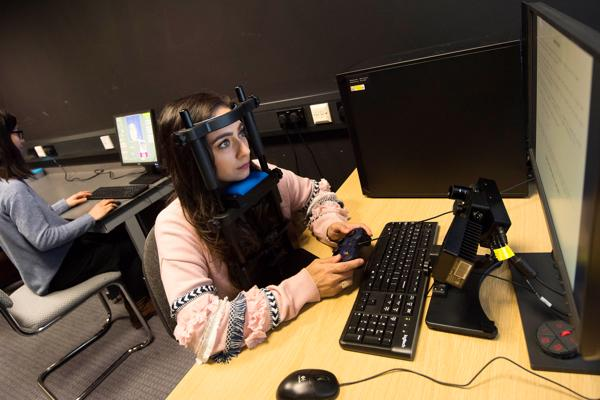 Psychology researcher wearing test equipment while working at a computer