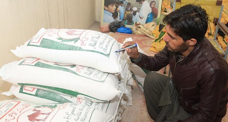 Carefully labelling bags of flour ready for distribution to participating households.