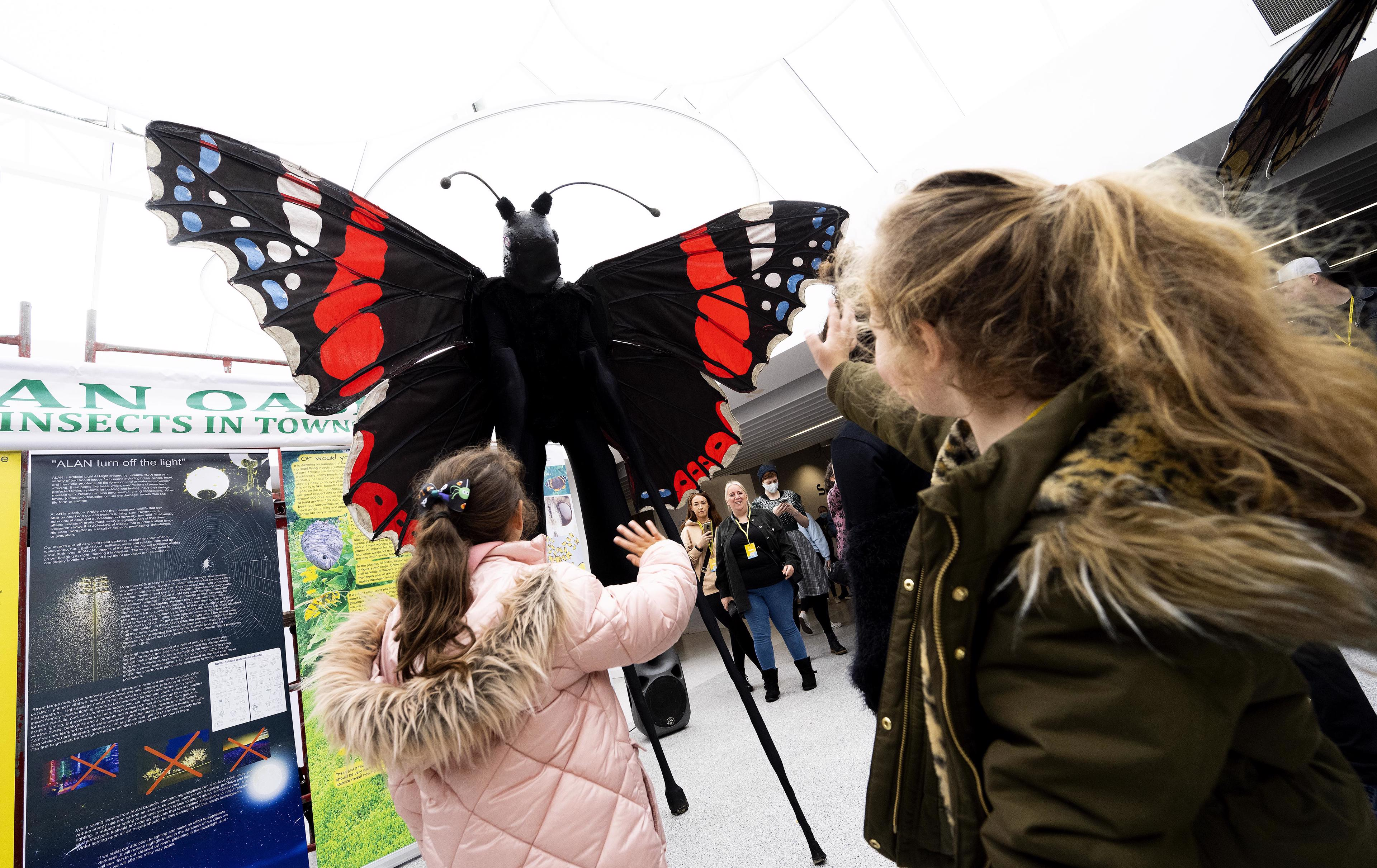 Red butterfly with waving children