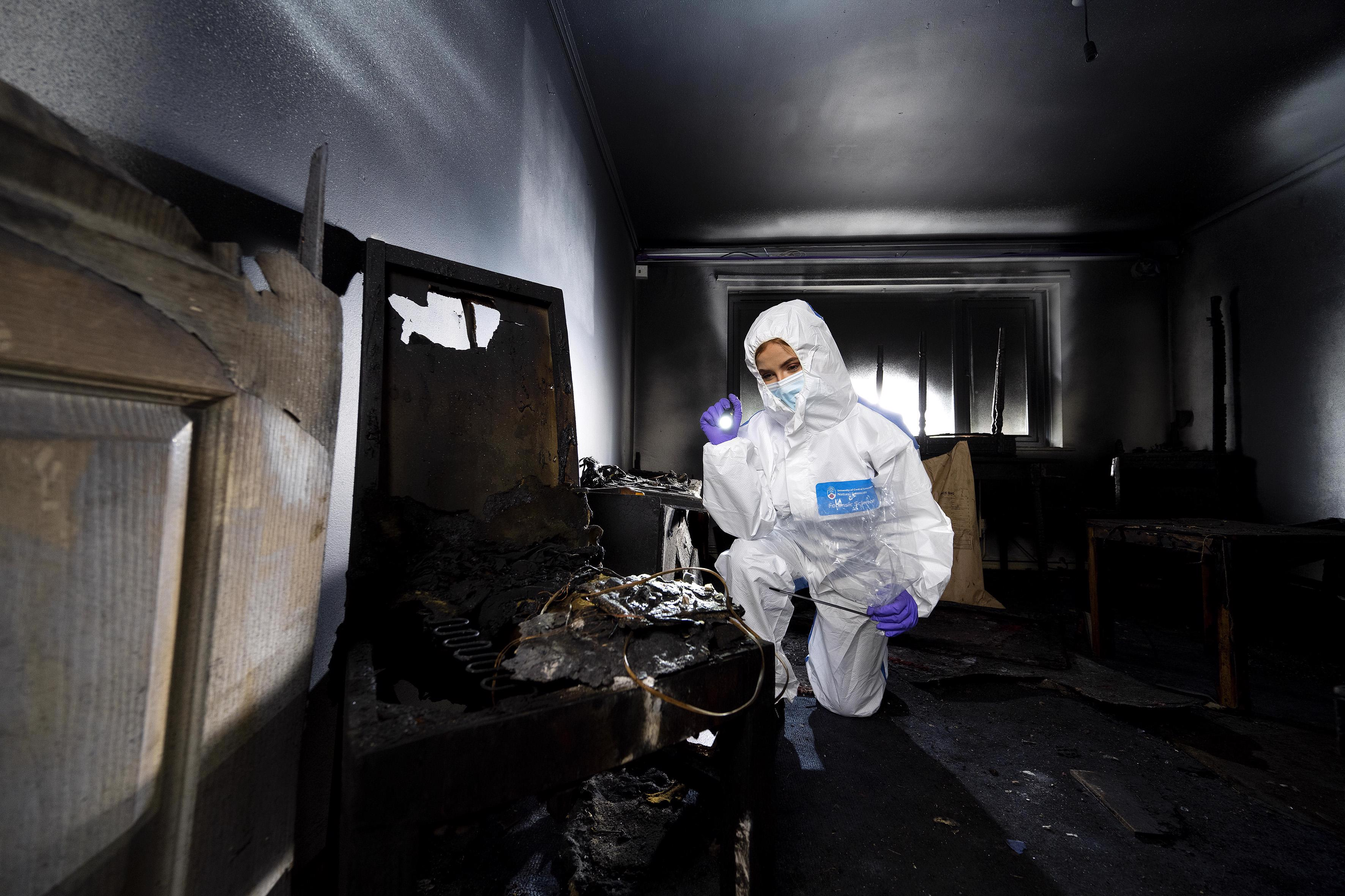 A student investigating in a fire damaged room