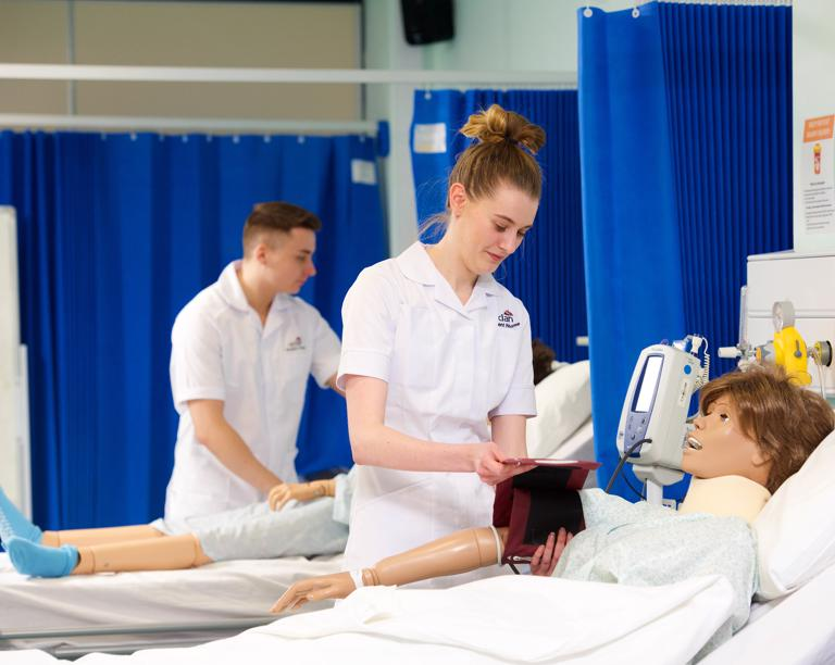 Two student nurses training with medical dummies.